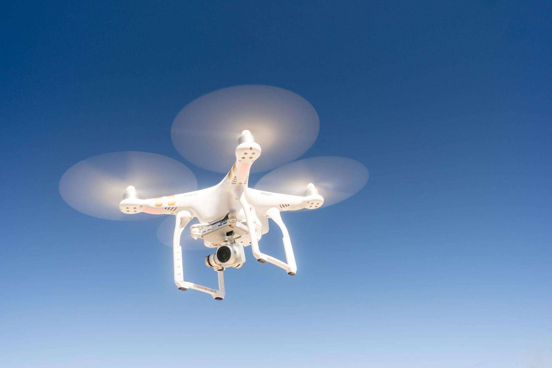 White Quadcopter Drone Flying Hovering Blue Sky
